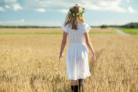 white dress: happiness, nature, summer holidays, vacation and people concept - smiling young woman in wreath of flowers and white dress walking along cereal field