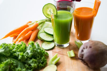 Alimentazione sana, bevande, dieta e disintossicazione concetto - stretta di occhiali con diversi succhi di frutta o di verdura e cibo sul tavolo Archivio Fotografico