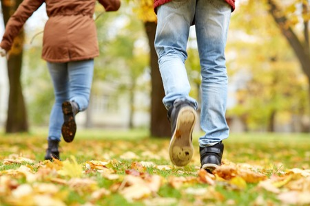 runaway: love, relationships, season and people concept - young couple running in autumn park