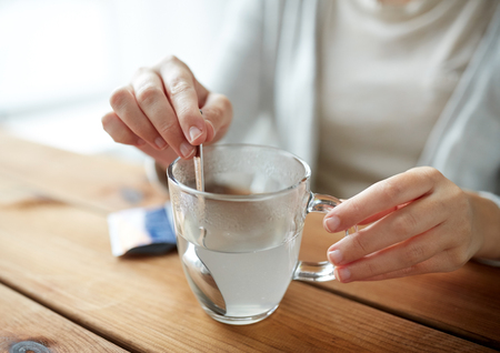 dissolve: healthcare, medicine and people concept - woman stirring medication in cup of water with spoon