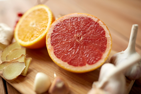 indigenous medicine: traditional medicine, cooking, food and ethnoscience concept - citrus fruits, ginger and garlic on wooden background Stock Photo