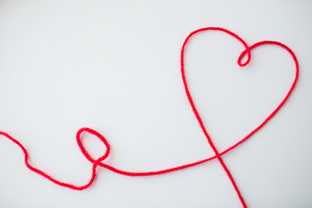hilo rojo: handicraft, love, valentines day, healthcare and needlework concept - red knitting yarn thread in shape of heart Foto de archivo