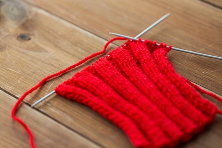 handicraft and needlework concept - hand-knitted item with knitting needles on wood Stock Photo