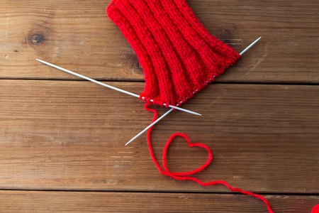 handicraft, love, valentines day and needlework concept - hand-knitted item with knitting needles and thread in heart shape on wood
