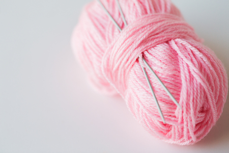 handicraft and needlework concept - knitting needles and ball of pink yarn on white