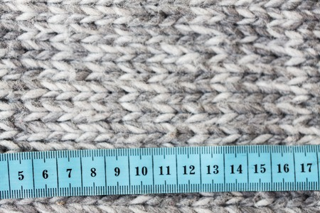knitwear: handicraft, knitwear and needlework concept - close up of knitted item with measuring tape