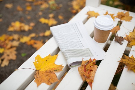 gazette: season and news concept - newspaper and coffee cup on bench in autumn park