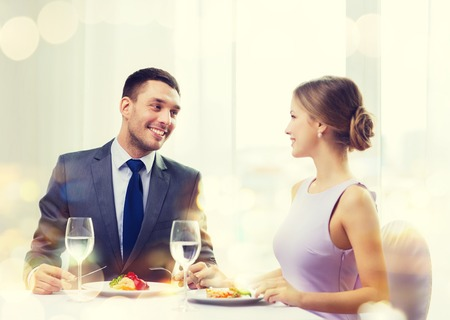 main course: restaurant, couple and holiday concept - smiling couple eating main course at restaurant Stock Photo