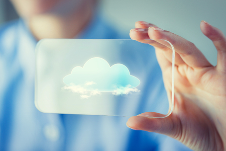 transparent system: business, technology, computing and people concept - close up of woman hand holding and showing transparent smartphone with cloud icon on screen Stock Photo