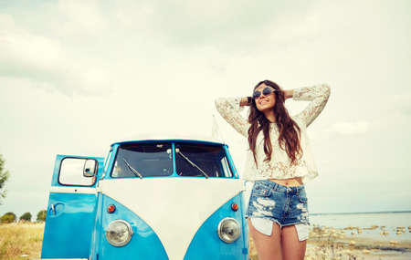 travel woman: summer holidays, road trip, vacation, travel and people concept - smiling young hippie women in minivan car Stock Photo