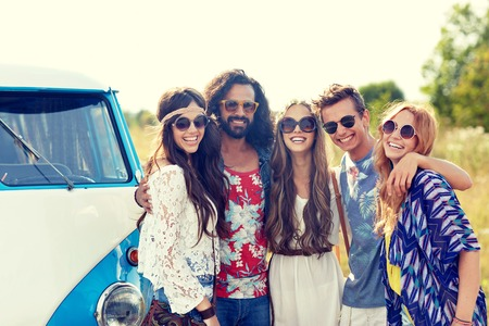 minivan: summer holidays, road trip, vacation, travel and people concept - smiling young hippie friends hugging over minivan car