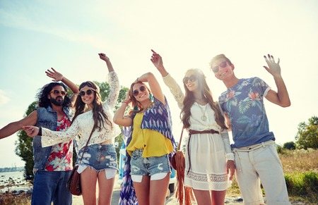 groovy: nature, summer, youth culture and people concept - happy young hippie friends dancing outdoors