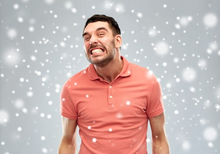 emotion, anger, winter, christmas and people concept - angry man over snow on gray background