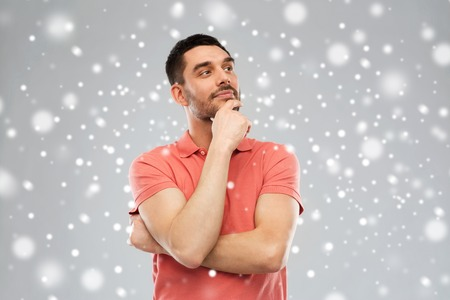 winter, christmas and people concept - man in polo t-shirt thinking over snow on gray background