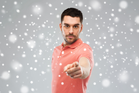emotion, gesture, winter, christmas and people concept - angry man pointing finger to you over snow on gray background
