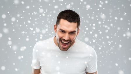 insulting: emotion, anger, winter, christmas and people concept - angry man over snow on gray background