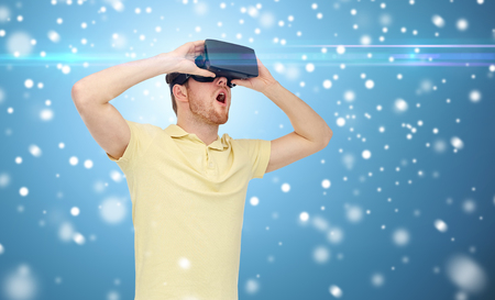 mediated: technology, augmented reality, winter, christmas and people concept - happy young man with virtual headset or 3d glasses playing game over snow on blue background and laser light