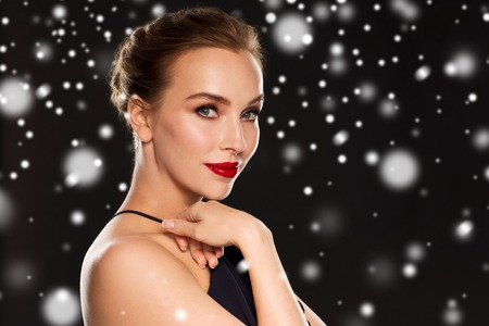 femme fatale: people, christmas, holidays, luxury and fashion concept - beautiful woman with red lips over black background and snow