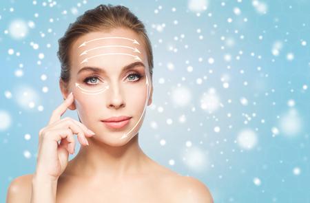 schoonheid, mensen, plastische chirurgie en anti-age concept - mooie jonge vrouw met het opheffen van pijlen op gezicht over blauwe achtergrond en sneeuw