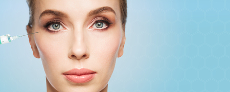 antiaging: people, cosmetology, plastic surgery, anti-aging and beauty concept - beautiful young woman face and syringe making injection to eye area over blue background