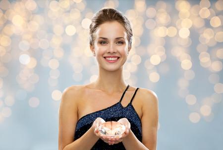 mensen, vakantie, juwelen en luxe concept - lachende vrouw in avondjurk en diamanten oorbellen over lichten achtergrond Stockfoto
