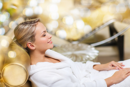 people and relaxation concept - beautiful young woman lying on chaise-longue in bath robe at spa over holidays lights background