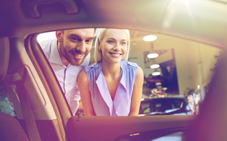 inside car: auto business, car sale, consumerism and people concept - happy couple buying car in auto show or salon