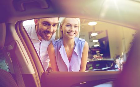 Auto Geschäft, Auto Verkauf, Konsum und Menschen Konzept - glückliches Paar Kauf Auto in Auto Show oder Salon Standard-Bild