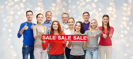 three generations of women: shopping, family, generation and people concept - group of happy men and women showing thumbs up and sale sign over holidays lights background