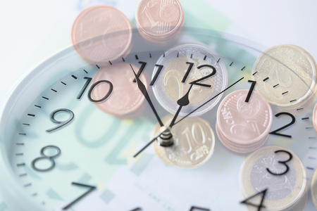 gaining: time, business, money making and finance concept - clock over euro coins and banknotes with double exposure effect