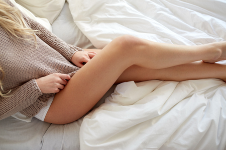 women legs: rest, sleeping, comfort and people concept - close up of young woman lying in bed at home