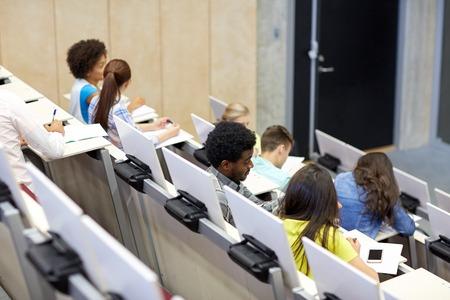 onderwijs, middelbare school, universiteit, leren en mensen concept - groep van internationale studenten praten in collegezaal