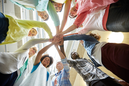 black hands: education, school, teamwork and people concept - group of international students with hands on top of each other over table
