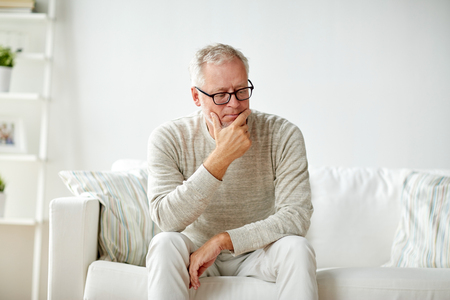mature man: old age, problem and people concept -  senior man in glasses thinking and sitting on sofa at home