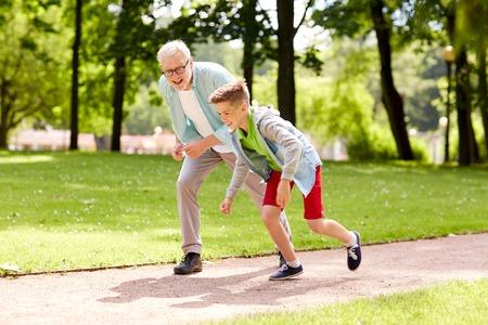 가족, 세대 및 사람들이 개념 - 행복 할아버지와 손자 여름 공원에서 경주 스톡 콘텐츠