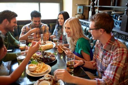 레저, 먹고, 음식 및 음료, 사람들이 및 휴일 개념 - 저녁 식사를하고 레스토랑 또는 펍에서 맥주를 마시는 웃는 친구