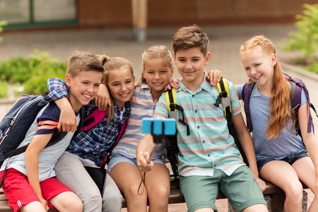 yard stick: primary education, technology, friendship, childhood and people concept - group of elementary school students with backpacks sitting on bench and taking picture by smartphone on selfie stick outdoors Stock Photo