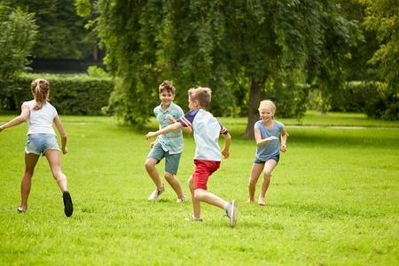 niñas jugando: la amistad, la infancia, el ocio y el concepto de personas - grupo de niños felices o amigos que juegan al juego de puesta al día y que se ejecutan en el parque de verano Foto de archivo
