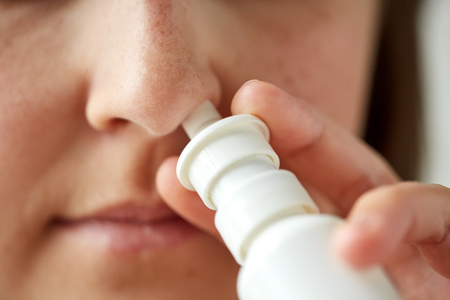 rheum: healthcare, flu, rhinitis, medicine and people concept - close up of sick woman using nasal spray Stock Photo
