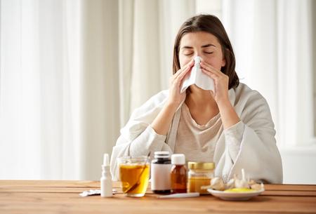 Les soins de santé, la grippe, l'hygiène, l'âge et le concept des personnes - une femme malade avec des médicaments soufflant le nez au papier essuyer à la maison