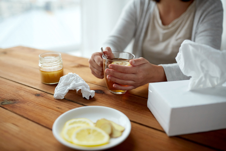 indigenous medicine: health, traditional medicine and ethnoscience concept - ill woman drinking tea with lemon and honey and paper wipes box on wooden table