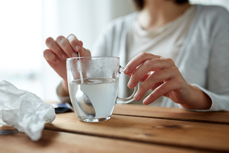 healthcare, medicine and people concept - close up of woman stirring medication in cup with spoon Фото со стока