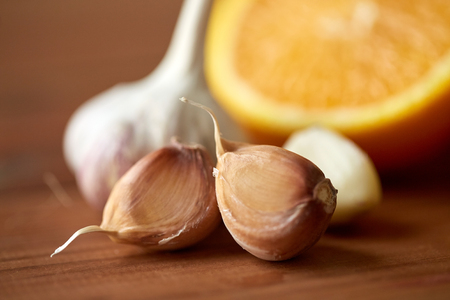 indigenous medicine: health, food, cooking, traditional medicine and ethnoscience concept - close up of garlic and orange on wooden table