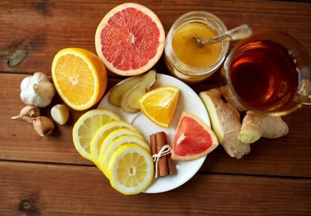 indigenous medicine: health, traditional medicine, folk remedy and ethnoscience concept - cup of ginger tea with honey, citrus and garlic on wooden background Stock Photo