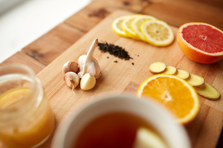 traditional remedy: health, traditional medicine, folk remedy and ethnoscience concept - cup of ginger tea with honey, citrus and garlic on wooden background Stock Photo