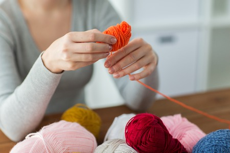acrylic yarn: knitting, people and needlework concept - woman pulling yarn up into ball Stock Photo