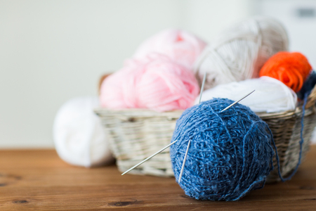 domestic life: handicraft and needlework concept - wicker basket with knitting needles and balls of yarn Stock Photo