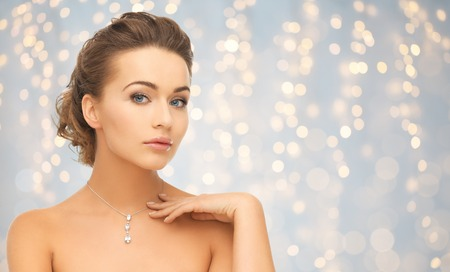 beauty, luxury, people, holidays and jewelry concept - beautiful woman wearing shiny diamond pendant over lights background
