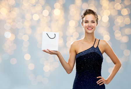 luxury, advertisement, holydays, people and sale concept - smiling woman with white blank shopping bag over lights background Stock Photo