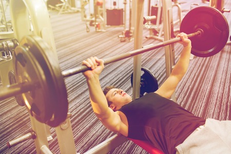 pesas: sport, bodybuilding, lifestyle and people concept - young man with barbell flexing muscles and making bench press in gym